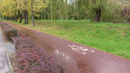 Bike lane sighn on a red bicycle path in a park after rain