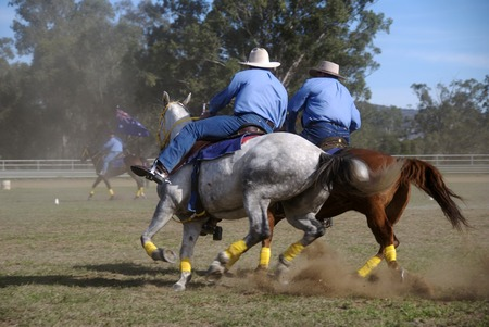 Two horsemen riding side by side at a country fair photo