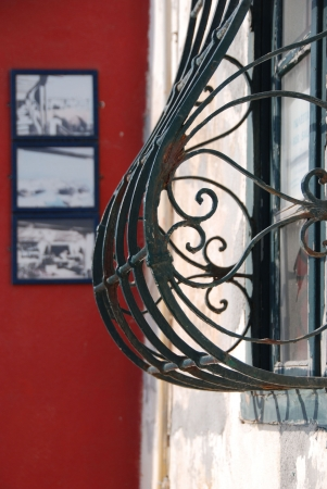 Wrought iron window in frontof a red wall with old photos