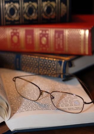 A pair of reading glasses on a book with a stack of old books in the background photo