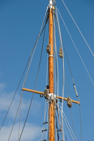 Top part of a wooden sailing mast or spar against a blue sky, with rigging (stays, lanyards, spreaders, strouds and ratlines). Stock Photo