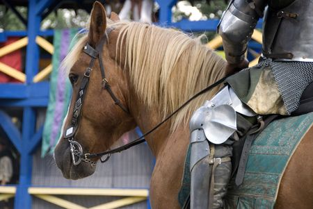 Close up of a knight in armors leg and torso as he waits to do battle in a joust atop his beautiful horse.