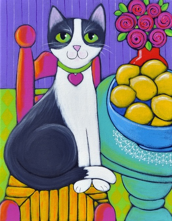 A black and white cat sitting next to a table that has a big blue bowl full of lemons on it. She is wearing a collar with a heart  photo