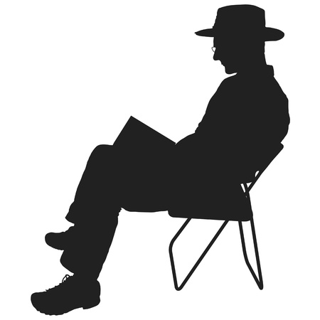 man holding book: Silhouette of a man reading. He is sitting in a chair and wearing a hat and glasses