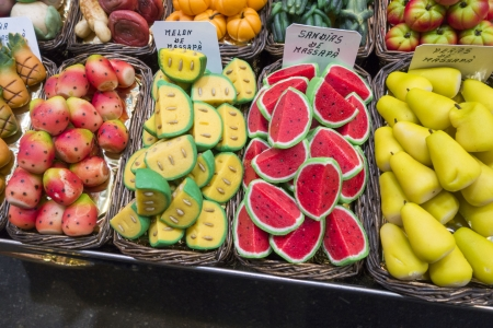 An assortment of fruit shaped marzipan in baskets at a market Foto de archivo
