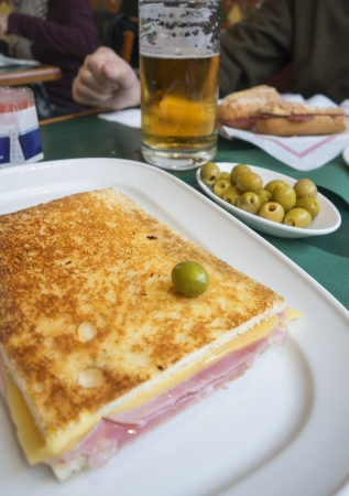 A large ham and cheese sandwich served with a bowl of olives