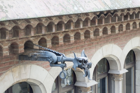 A metal gargoyle on a building in Barcelona Foto de archivo