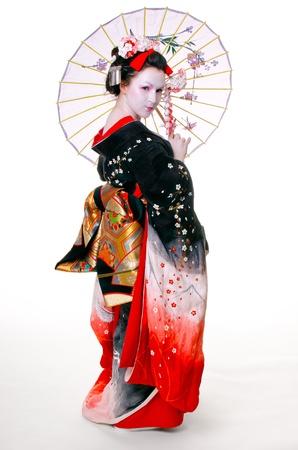 geisha with umbrella in kimono on an isolated white background
