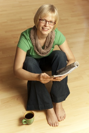 bare feet girl: young blonde woman sitting barefoot on the floor reading a magazine