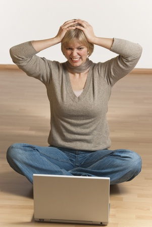 angry blonde: young woman sitting on the floor  having trouble with her computer
