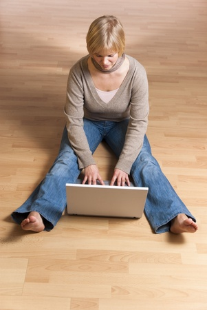 young woman with computer sitting barefoot on the floor, view from above photo