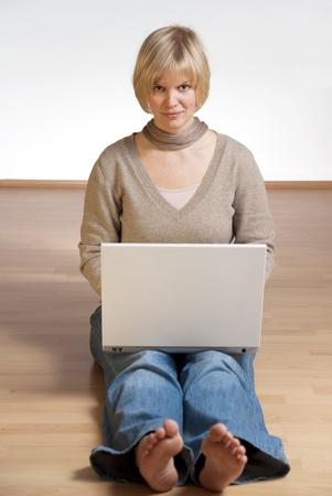piedi nudi di bambine: giovane studente a piedi nudi a lavorare sul suo computer Archivio Fotografico