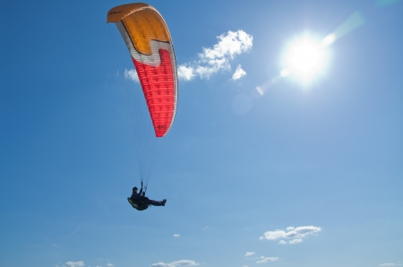 paragliding: paraglider flies into the sun Editorial