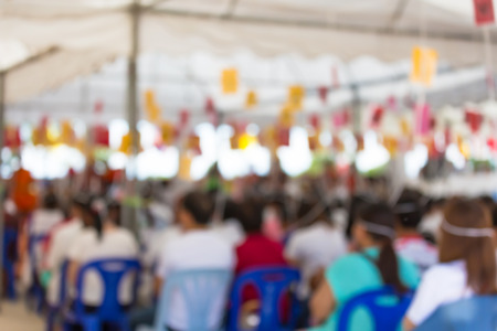pubic: Defocus of people sit with hands clasped and put holy thread on their head for merit in lamphun thailand temple pubic location