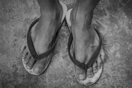 pieds sales: Pieds noirs et blancs dans des sandales et sale vieux avec un fond en b�ton Banque d'images