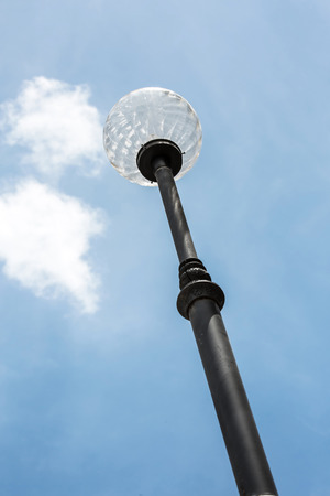 sunligh: looking up to spotlight post with blue sky, round street light