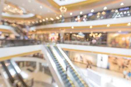 Blurred people stand on escalator in the interior shopping mall for business banner background