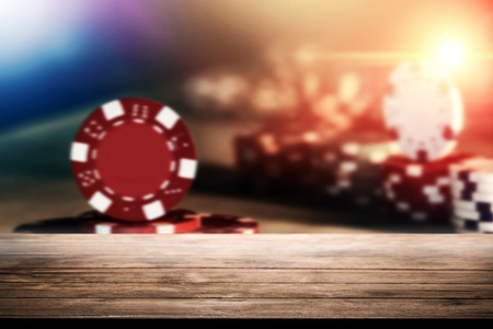 Empty wooden tabletop over poker chips on the table in casino vintage background for product montage product. Stock Photo
