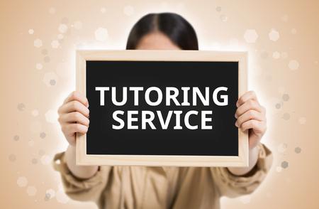 undergraduate: Tutoring Service text on chalkboard in child hands.
