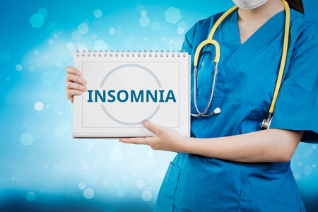 Doctor shows Insomnia text on white line paper book. Stock Photo