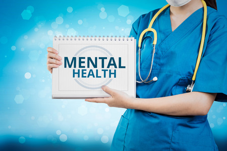 Doctor shows Mental Health text on white line paper book. Stock Photo