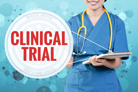 clinical trial: Smile female doctor with blurry blue glitter point to text: Clinical Trial