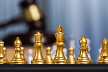 Close up golden king of chess or checkers with blurry gavel meaning fighting, justice and victory for lawyer job background.