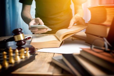Jeune homme avocat consultant avec le travail d'équipe par vidéoconférence sur mobile et lire un livre d'avocat dans le bureau de travail avec effet de lumière du soleil dans le ton vintage de la photographie.