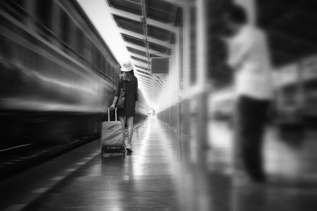 Black and White, Voyeur unknow person following for take a photo the tourist woman at train station. Stock Photo