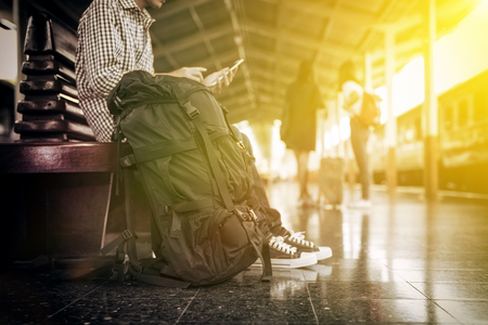 waiting phone call: Young male asian traveler go to travel vacation by train, the travel man with backpacking sitting at train station, side view photography, vintage style of image with sunlight effect.
