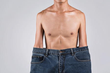 thinness: A man in bigger jeans with thin body, asian man in studio photography.