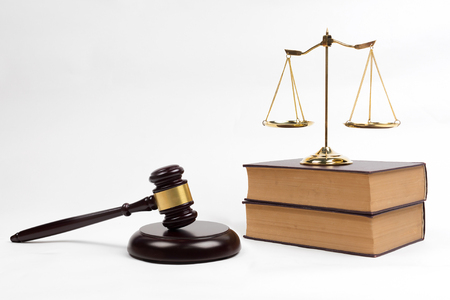 Gavel, golden scales, lawyer books on white background.
