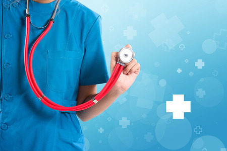 Medital female health care professional nurse or portrait of doctor holding up stethoscope on blue abstract icon background.  Stock Photo
