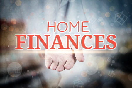 Man hand holding Home Finances text on blurry home icon property background. Stock Photo
