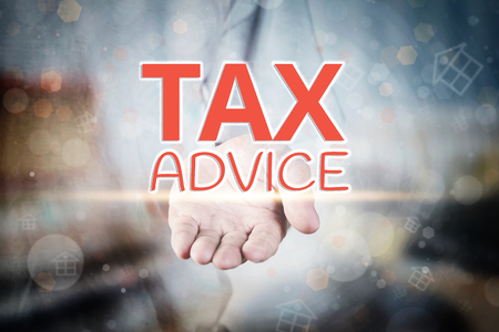 tax tips: Man hand holding Tax Advice text on blurry home icon property background.