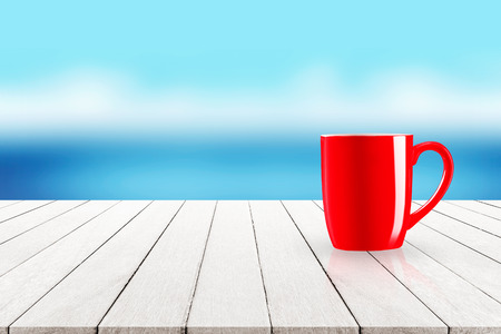 Red coffee mug on empty wooden tabletop with blurry blue ocean seascape with white clouds summer background.