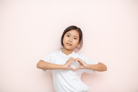 intelligently: Asian tanned skin girl child portrait over pink wall background, valentine day concept.