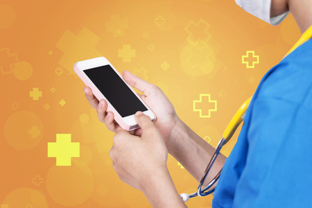 diagnose: Female nurse using pink mobile dark screen over abstract orange with hospital icon background. Stock Photo