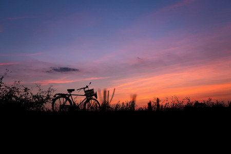gloaming: Bicycle silhouette in nature sunset golden hour evening with twilight sky background. Stock Photo
