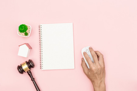 Top view lawyer desk, object on pink background with man hand holding white computer mouse. Stock Photo
