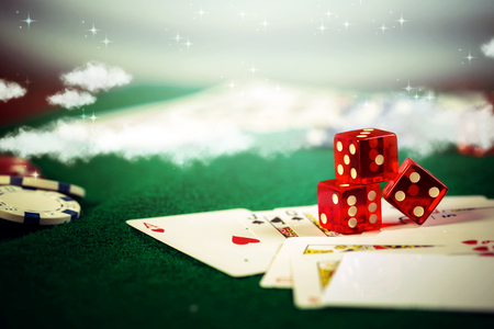 Casino dice with poker chips in gamble green table.