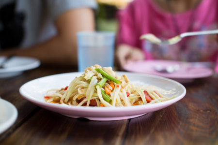 Father and daughter eating papaya salad on sunday holiday weekend. Stock Photo