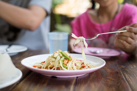 Young daughter asian have a dinner with her father at papaya salad restaurant on sunday weekend.
