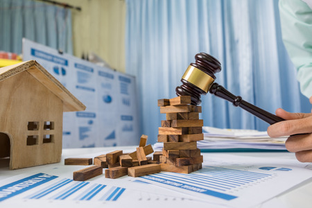 El concepto de las propiedades inmobiliarias, previene el consultor urgente, el juguete de madera que construye en la tabla del escritorio de negocio en oficina.
