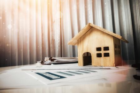 Casa y propiedad en concepto de venta, juguete de casa de madera en el escritorio de oficina.