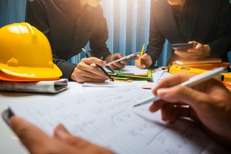 Trabajo en equipo de la reunión de trabajo del contratista del hombre de negocios en el sitio de construcción de la oficina en su proyecto del arquitecto.
