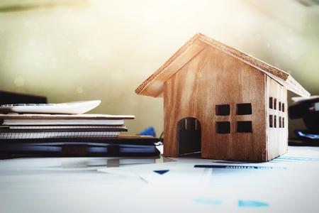 Huis en onroerend goed te koop concept, houten huis speelgoed op kantoor bureau. Stockfoto
