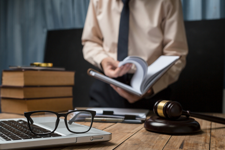 law suit: Business lawyer working hard at office desk workplace with book and documents. Stock Photo