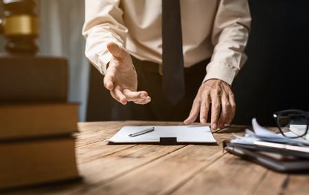 Zakelijke advocaat werkt hard op kantoor werkplek met boek en documenten.