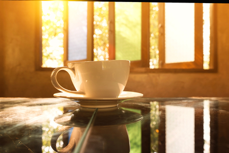 retailer: Coffee cup at coffee shop on glasses table with old vintage wooden window background.